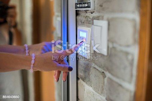 istock Woman entering password on home alarm keypad. 854643650