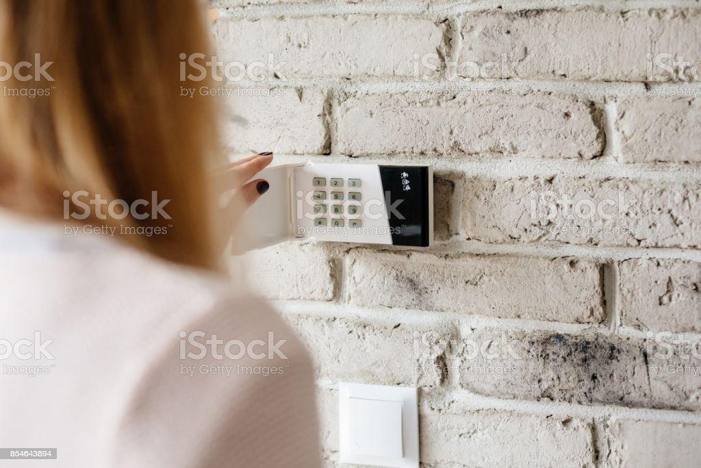 Woman entering password on home alarm keypad. stock photo