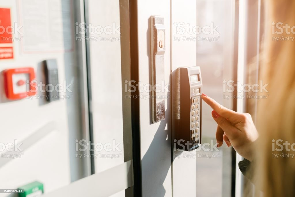 Woman entering pin code to security system stock photo