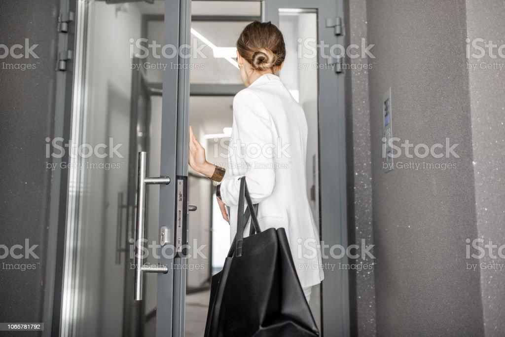 Femme entrant dans le bâtiment résidentiel - Photo