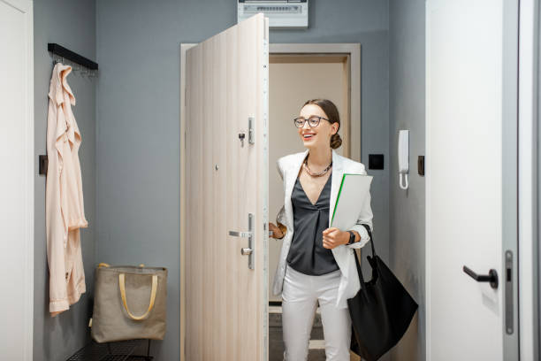 Woman entering the apartment Young business woman entering the apartment returning from the work to home entering stock pictures, royalty-free photos & images