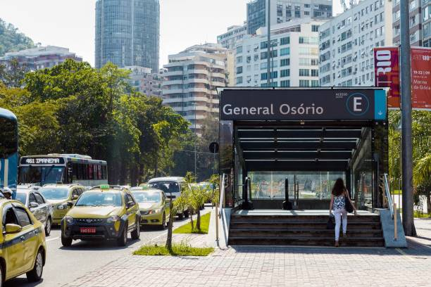 Woman entering the subway station Rio de Janeiro, Brazil - September 17, 2019 - Young woman enters the Lagoa entrance of Gerneral Osório subway station besides the trafic jam with taxi and buses. lagoa rio de janeiro stock pictures, royalty-free photos & images