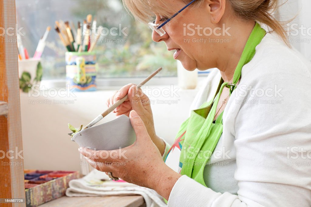 Woman enterpreneur working on ceramic bowl stock photo