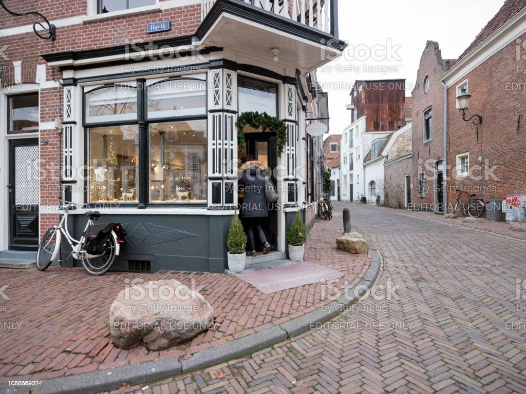 vrouw komt van oude winkel in middeleeuwse centrum van amersfoort en verlaat fiets buiten foto