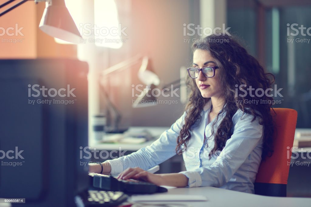 Woman entrepreneur busy with her work in office. Woman entrepreneur busy with her work in office Adult Stock Photo
