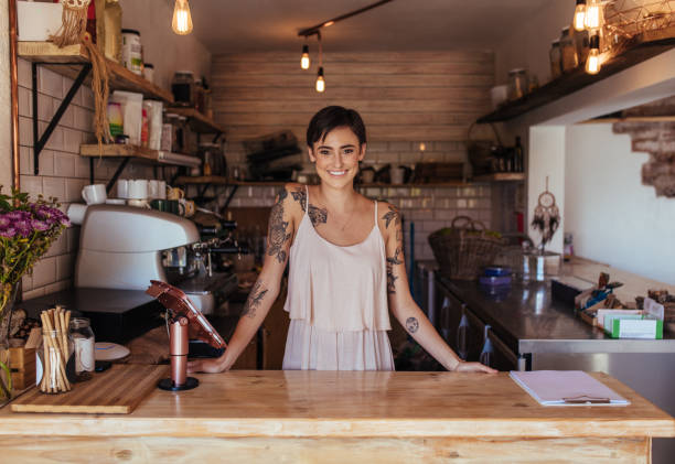 Woman entrepreneur standing at the billing counter of her cafe stock photo