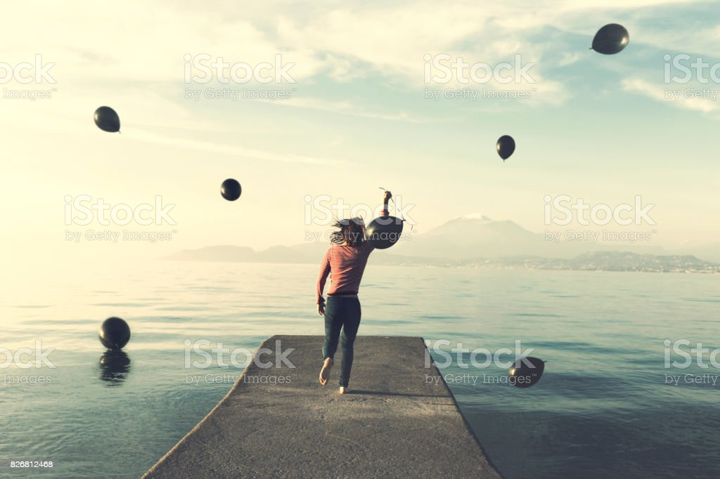 Woman escaping from a rain of black balloons towards the infinite with the ballon she chosing to carry with her stock photo