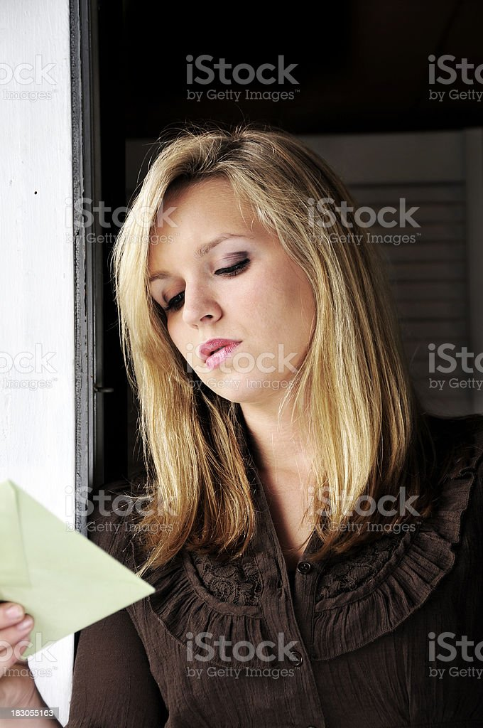 Woman Examines a Piece of Mail with Concern stock photo