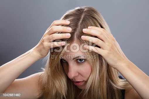 istock Woman Examining Her Hair 1042651462