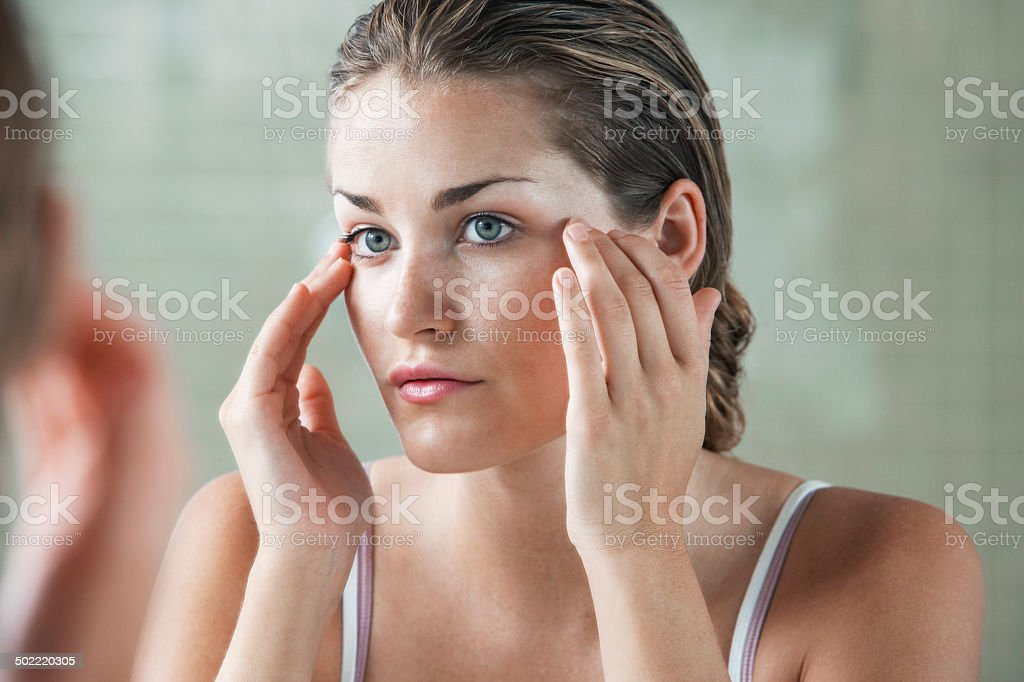 Woman Examining Herself In Front Of Mirror stock photo
