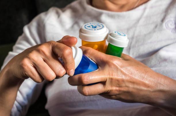 frau untersucht medikamentöse behandlung, mehrere boote in der hand, konzeptbild - spanische rezepte stock-fotos und bilder