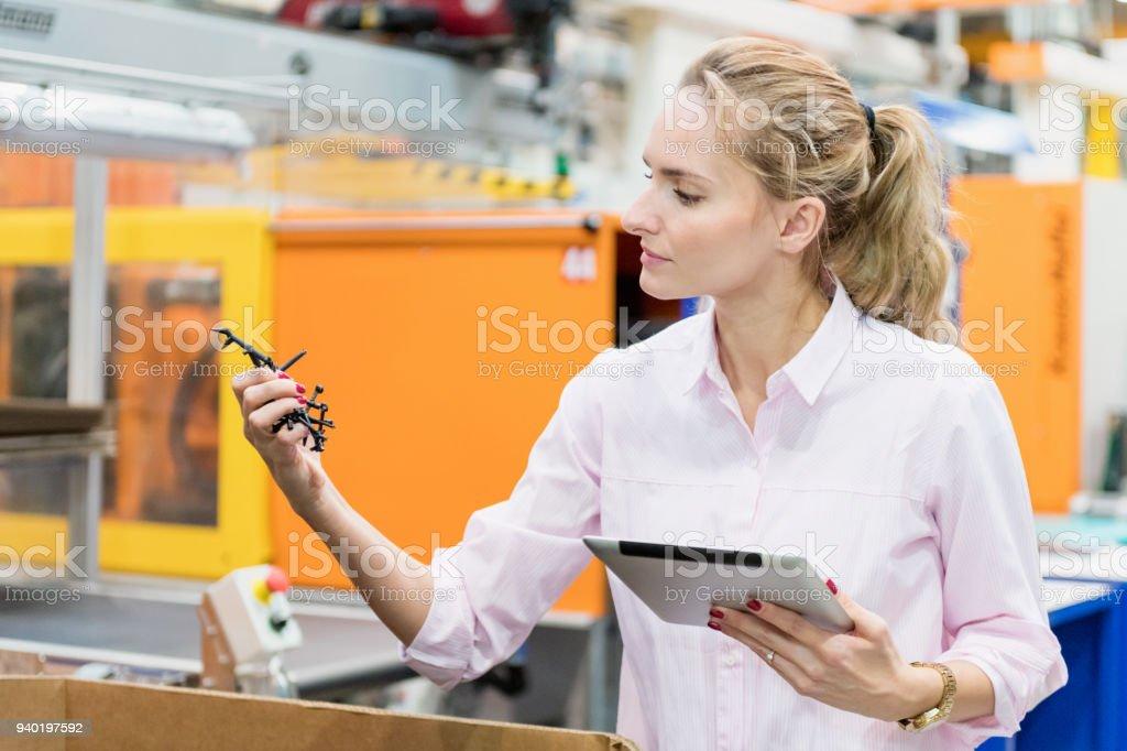 Frau, die Prüfung der Qualität von Kunststoff-Produkt – Foto
