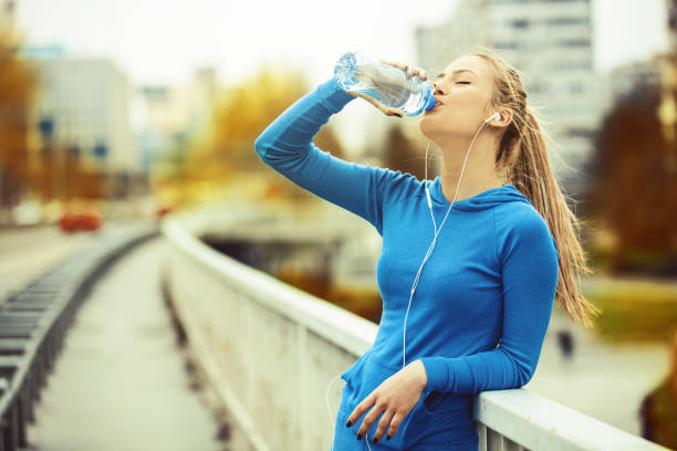 woman exercise on the bridge - drinking water stock photos and pictures