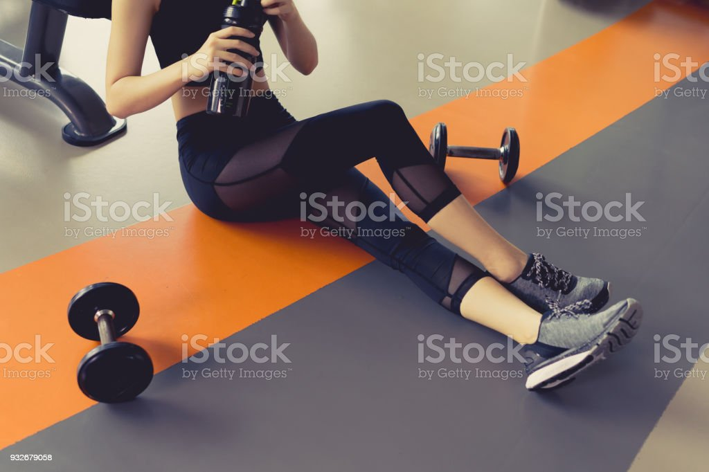 Woman exercise workout in gym fitness breaking relax after training sport with dumbbell and protein shake bottle healthy lifestyle bodybuilding stock photo