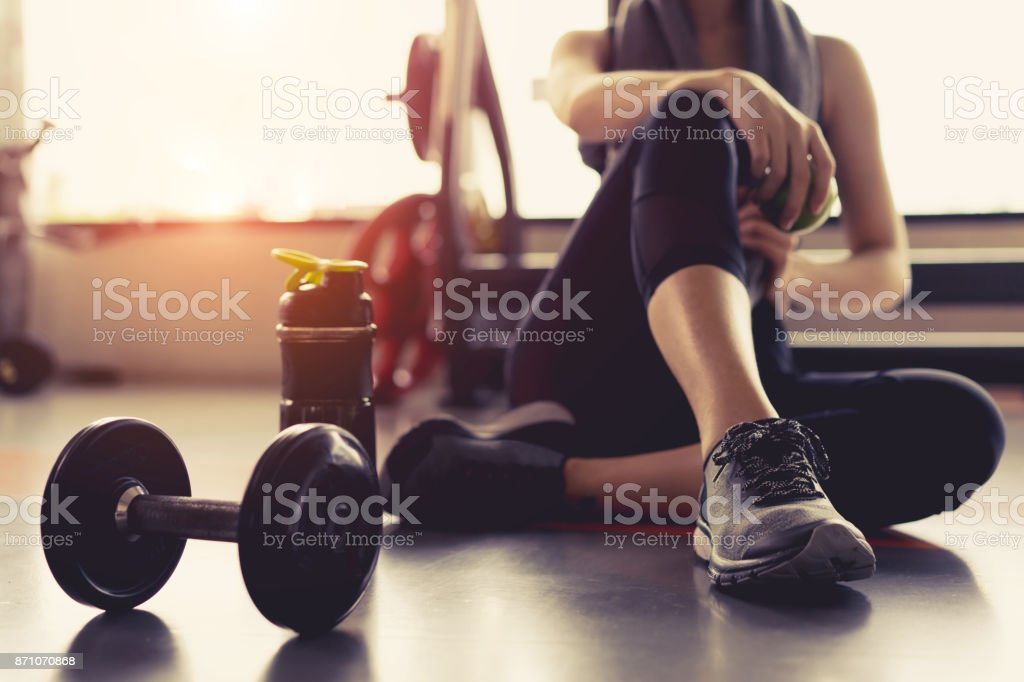 Woman exercise workout in gym fitness breaking relax holding apple fruit after training sport with dumbbell and protein shake bottle healthy lifestyle bodybuilding. stock photo
