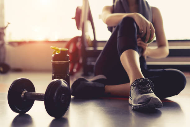 woman exercise workout in gym fitness breaking relax holding apple fruit after training sport with dumbbell and protein shake bottle healthy lifestyle bodybuilding. - weights stock photos and pictures