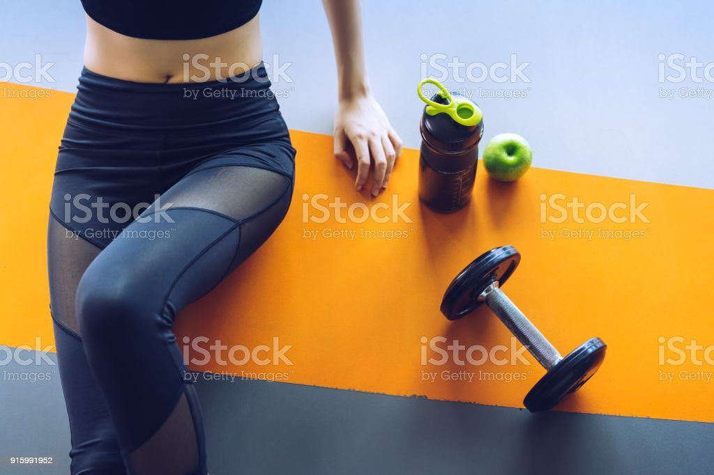 Woman exercise workout in gym fitness breaking relax with apple fruit after training sport with dumbbell and protein shake bottle healthy lifestyle bodybuilding, Top view Woman exercise workout in gym fitness breaking relax with apple fruit after training sport with dumbbell and protein shake bottle healthy lifestyle bodybuilding, Top view Adult Stock Photo