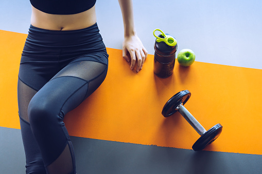 Woman Exercise Workout In Gym Fitness Breaking Relax With Apple Fruit After Training Sport With Dumbbell And Protein Shake Bottle Healthy Lifestyle Bodybuilding Top View Stock Photo - Download Image Now