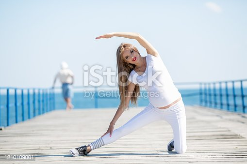 816941230 istock photo Woman exerciseons on the beach 1210109001