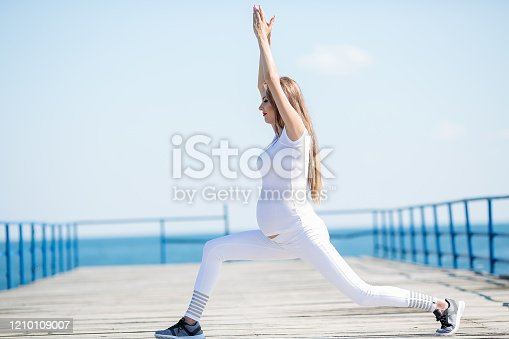 887354516istockphoto Woman exerciseons on the beach 1210109007