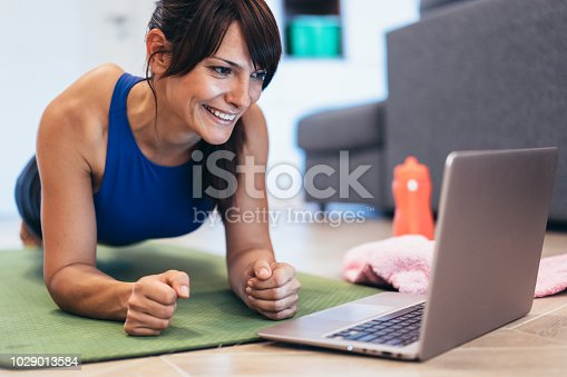 925799546 istock photo Woman exercising and looking at her lap top 1029013584