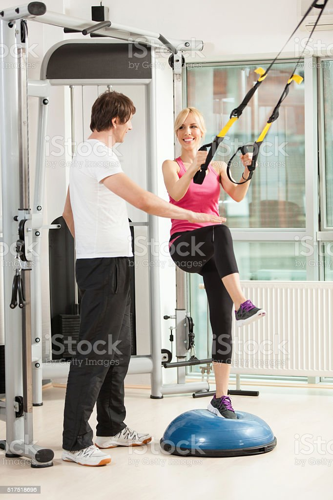 Woman exercising and talking to her instructor in a gym. stock photo