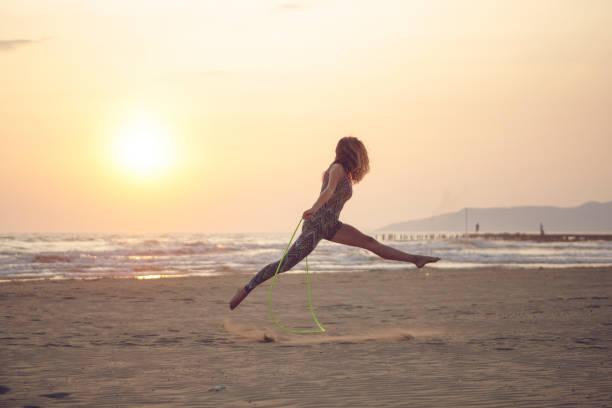 femme exerçant à la plage - éther photos et images de collection