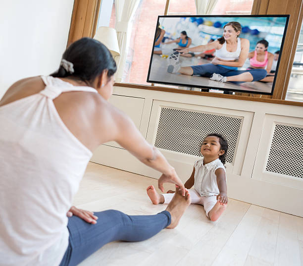 woman exercising at home and watching the baby - yoga videos stock-fotos und bilder