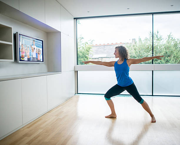 woman exercising at home watching a pilates dvd - yoga videos stock-fotos und bilder