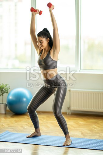 1035512048istockphoto Woman exercising at home with dumbbells 1195777273