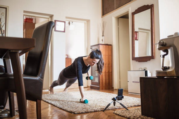 Woman exercising at home with online coach support stock photo