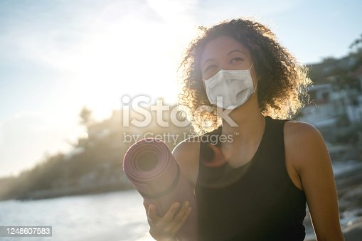 Portrait of a woman exercising at the beach wearing a facemask and holding a yoga mat – COVID-19 pandemic lifestyle concepts