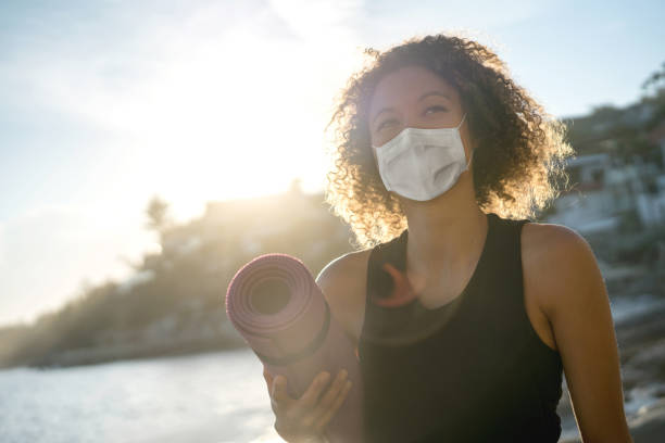 Woman exercising at the beach wearing a facemask and holding a yoga mat stock photo