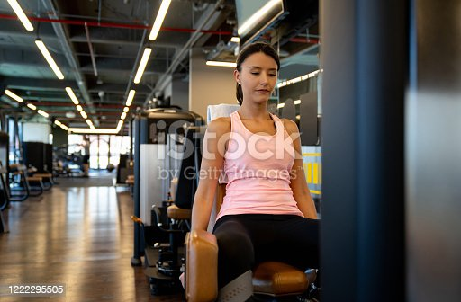 Athletic Latin American woman exercising at the gym using a machine to strengthen her inner-thighs