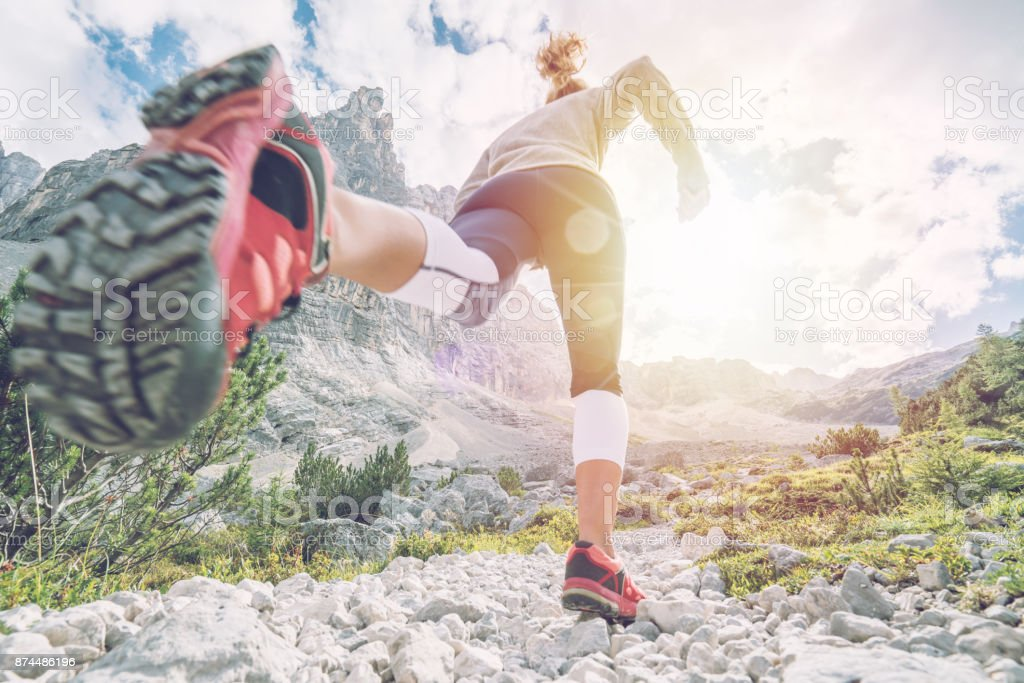 Woman exercising for cross-country running, dolomites, Italy stock photo