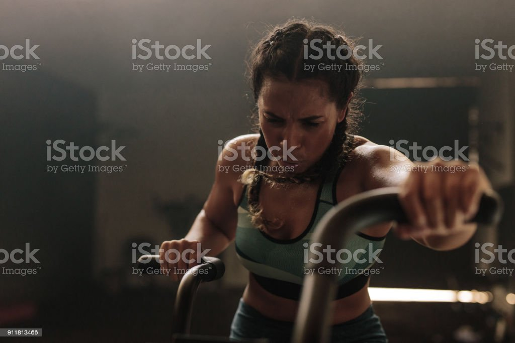 Woman exercising hard on gym bike stock photo
