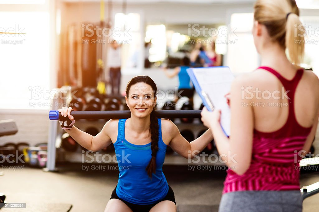 Woman exercising in gym, personal trainer, plan on clipboard royalty-free stock photo