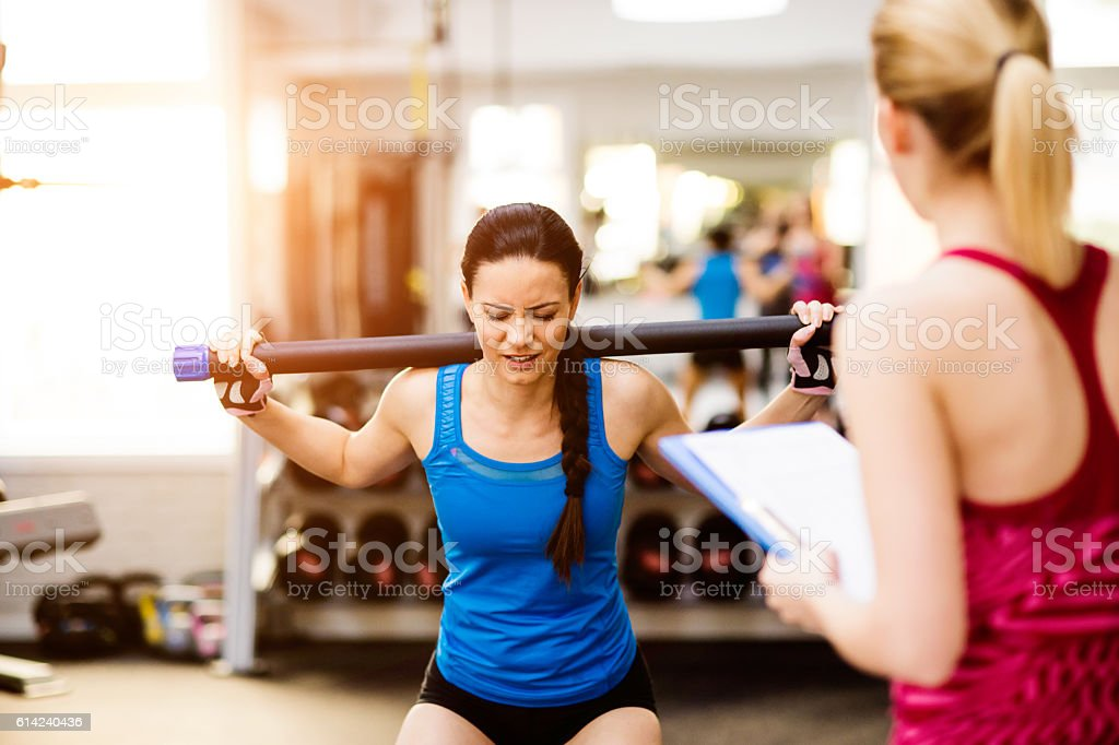 Woman exercising in gym, personal trainer, plan on clipboard stock photo