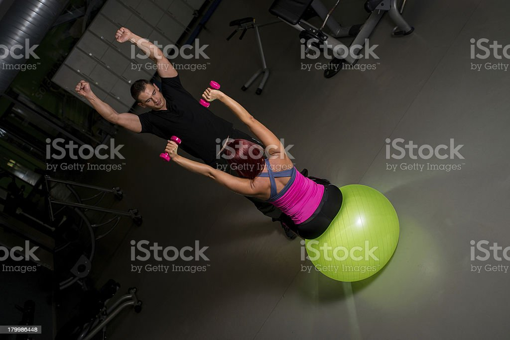 Woman exercising in gym with personal trainer royalty-free stock photo