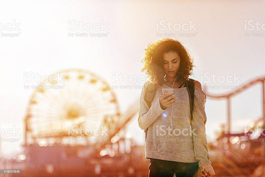 Donna esercizio in AAA usa uno smartphone, California - foto stock