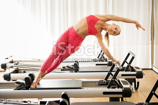 istock Woman exercising mermaid stretch on reformer bed 1171254735