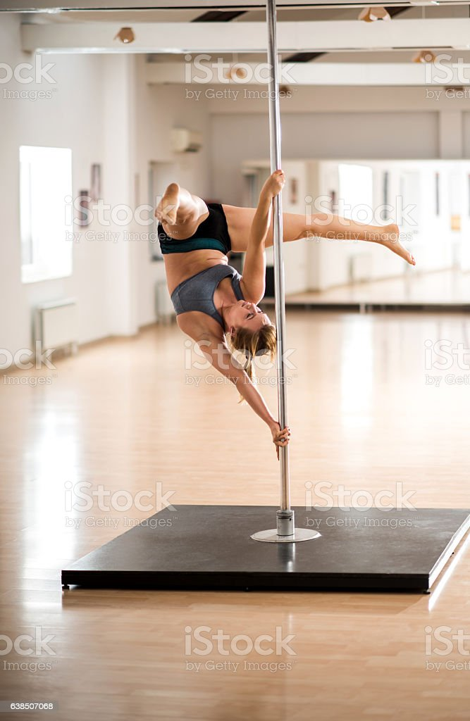 Woman exercising on a dancing pole in a studio. stock photo
