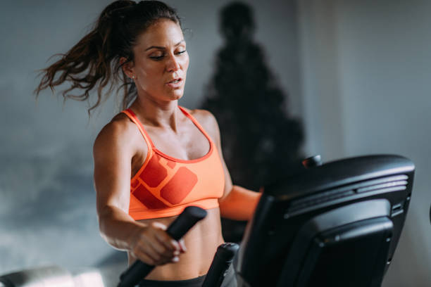 Woman Exercising on Elliptical Cross Trainer Woman Exercising on Elliptical Cross Trainer training equipment stock pictures, royalty-free photos & images