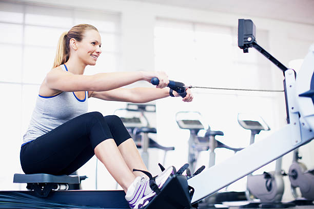Woman exercising on rowing machine in gymnasium  exercise machine stock pictures, royalty-free photos & images