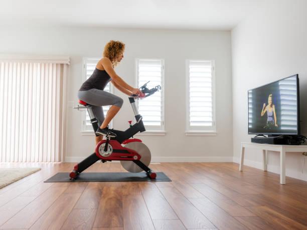 vrouw uit te oefenen op een spin fiets in huis - ronddraaien stockfoto's en -beelden