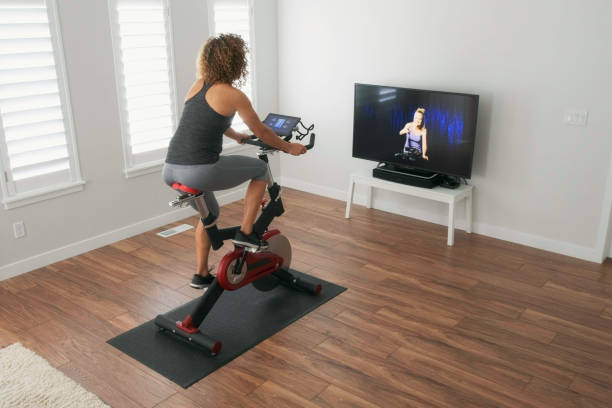 Woman Exercising on Spin Bike in Home A woman exercising on a spin bike using an online instructor inside a home. exercise bike stock pictures, royalty-free photos & images
