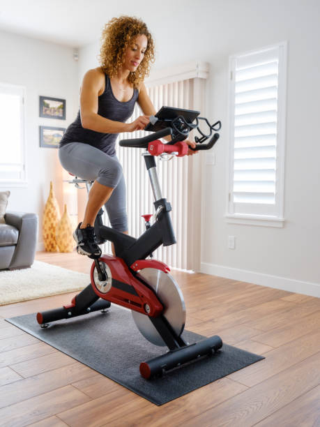 Woman Exercising on Spin Bike in Home A woman exercising on a spin bike using an online instructor inside a home. exercise machine stock pictures, royalty-free photos & images
