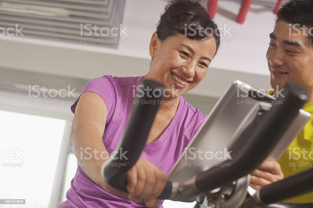 Woman exercising on the exercise bike with her trainer royalty-free stock photo