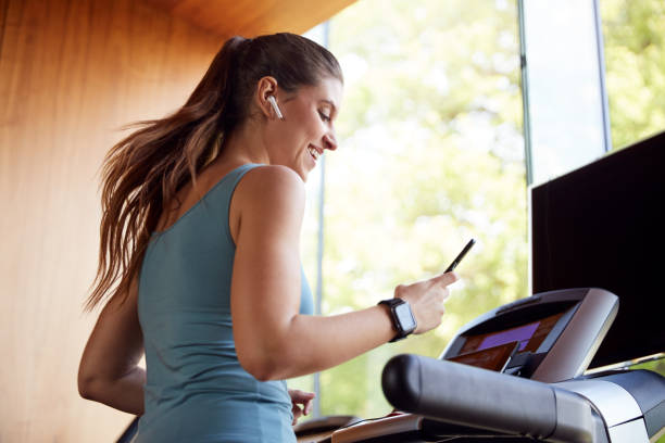 Woman Exercising On Treadmill Wearing Wireless Earphones And Smart Watch Checking Mobile Phone Woman Exercising On Treadmill Wearing Wireless Earphones And Smart Watch Checking Mobile Phone treadmill stock pictures, royalty-free photos & images