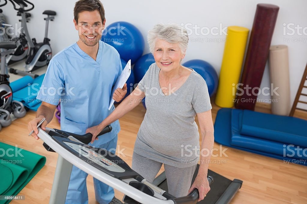 Woman exercising on treadmill with coach standing by stock photo